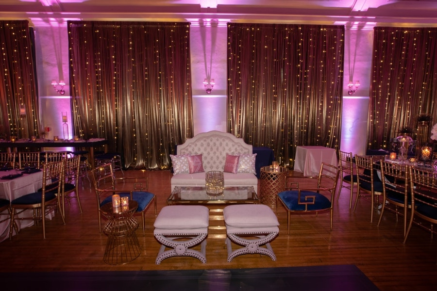 Gold party backdrop with pink lighting and decor