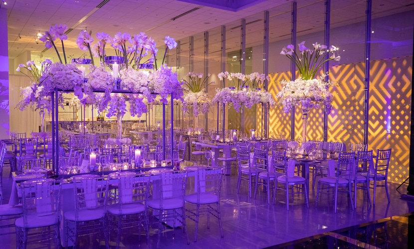 Purple lighting and white florals and chairs