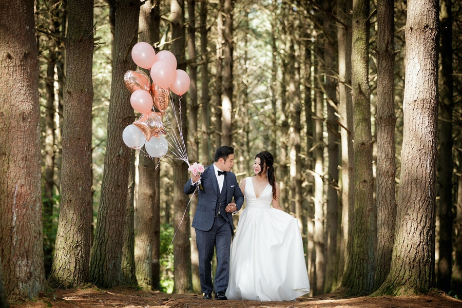 Couple in forest holding pink balloons