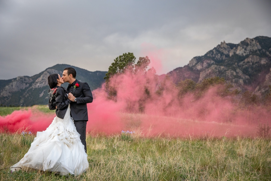 Couple kissing with pink smoke in the background