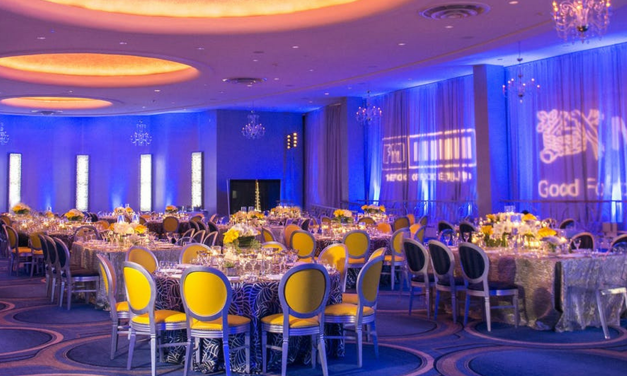 blue uplighting in miami beach ballroom with pops of yellow chairs and chandeliers