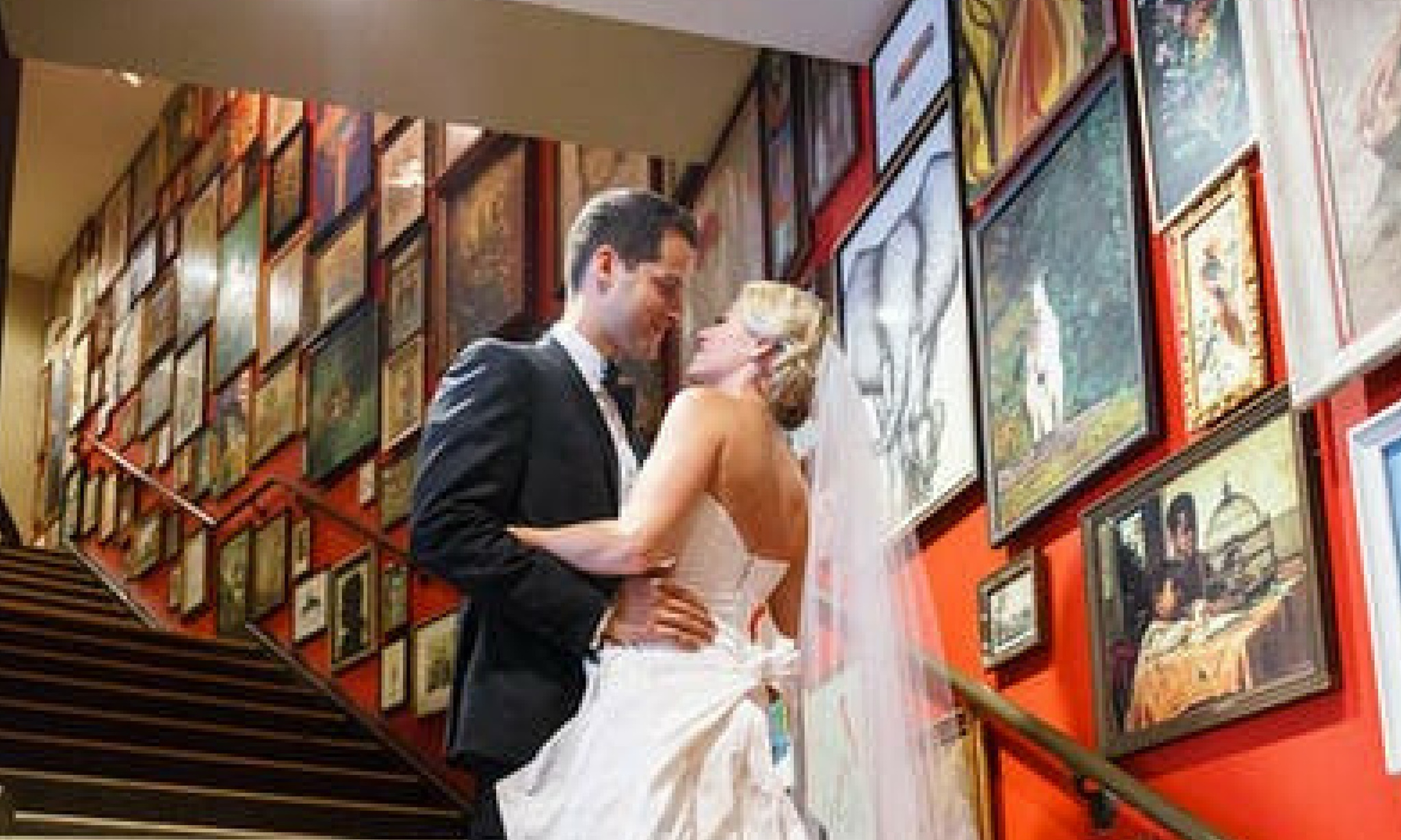 Bride and groom next to red wall covered in art at Hotel Lincoln Chicago
