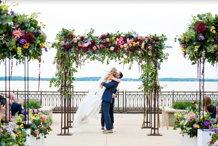 Couple kissing in front of flower arrangements