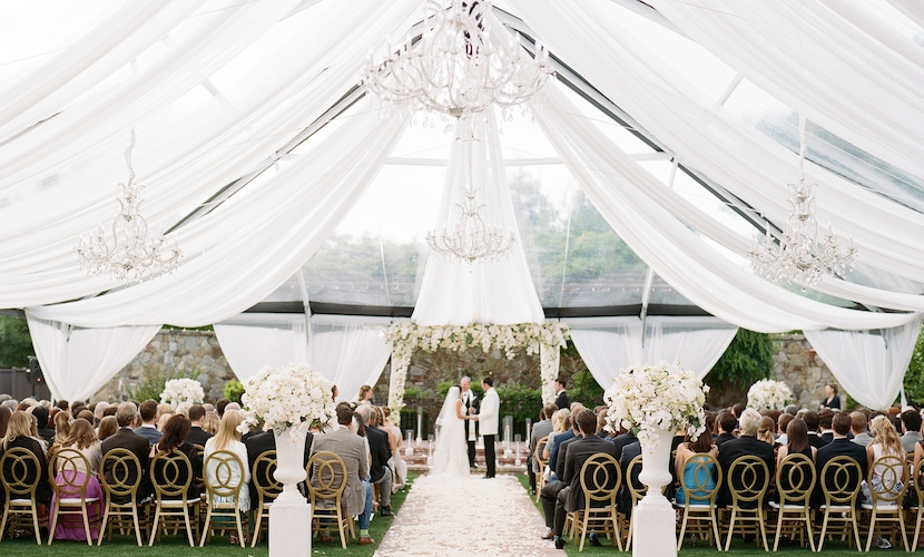 white tent wedding with greenery and brick aisle