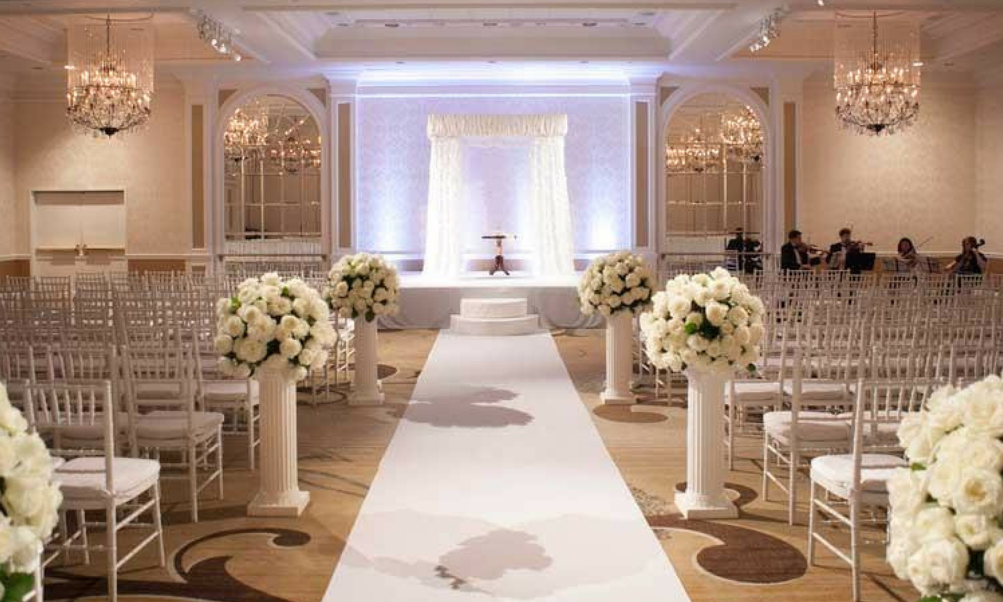 white wedding aisle with white roses and drapery at the fairmont