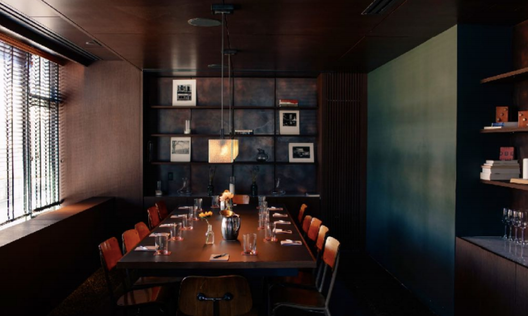 a naturally lit room with a dark stained wooden table, surrounded by earth toned decor