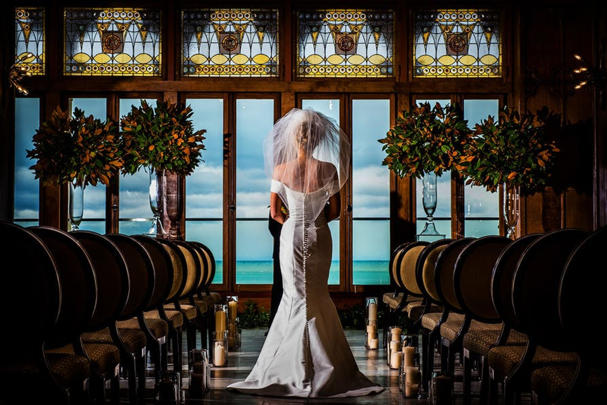 a bride walks down the aisle going towards huge windows looking over a wonderful view