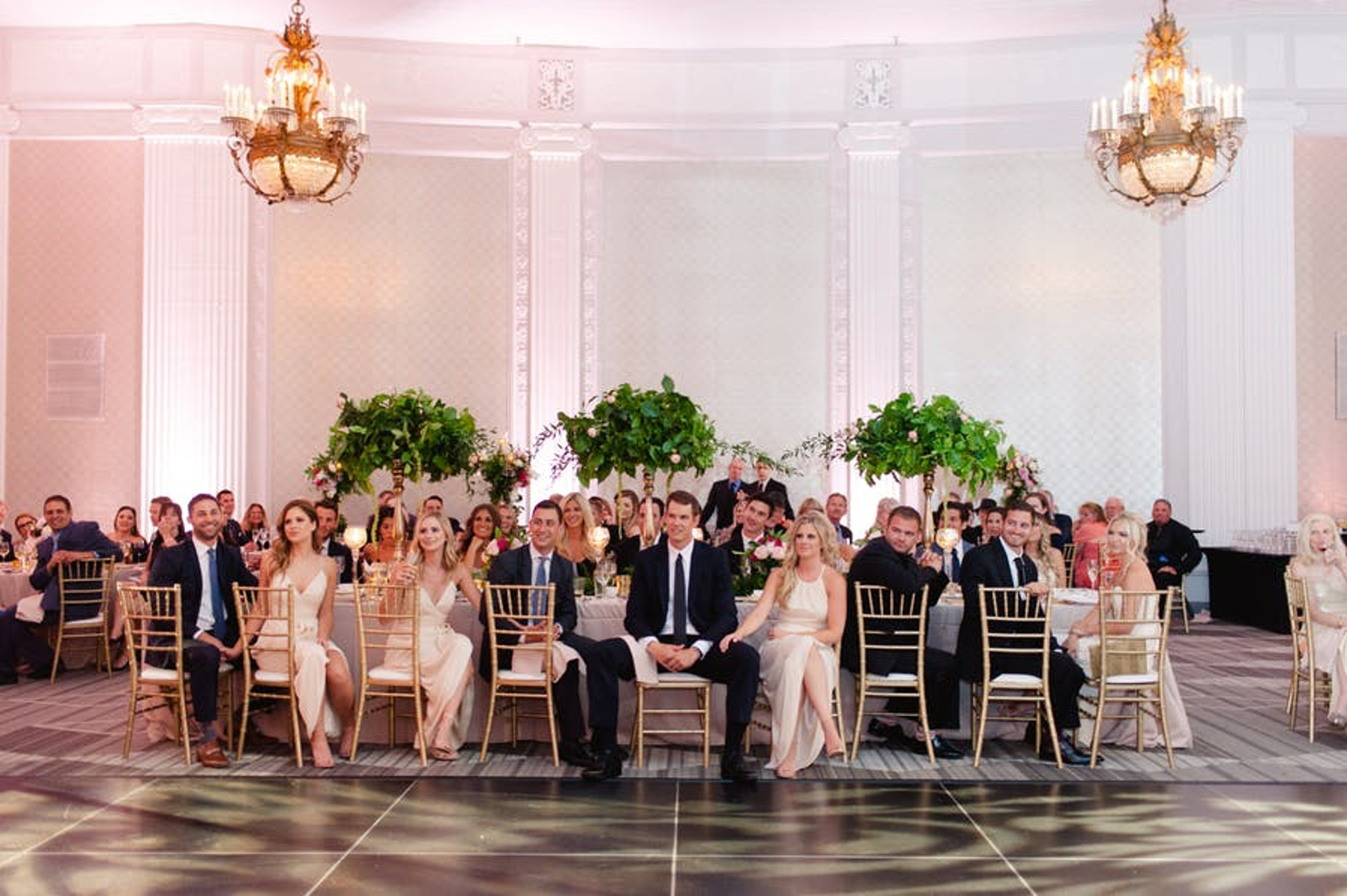 a ballroom hosts a table of people with greenery in the background