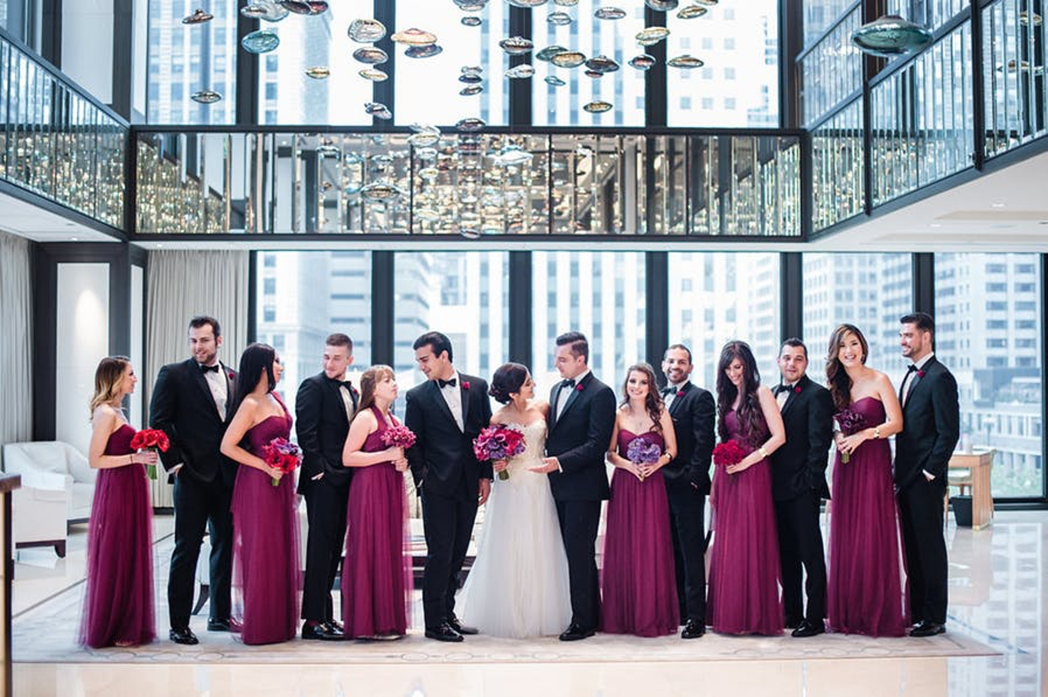 the bridal party is posed in the langham with massive windows behind them
