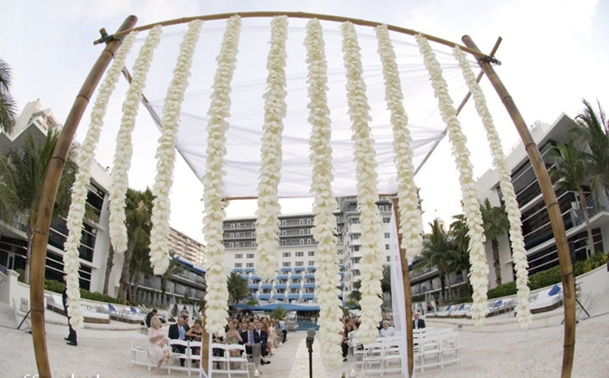 hanging strings of white flowers at beach wedding ceremony south beach