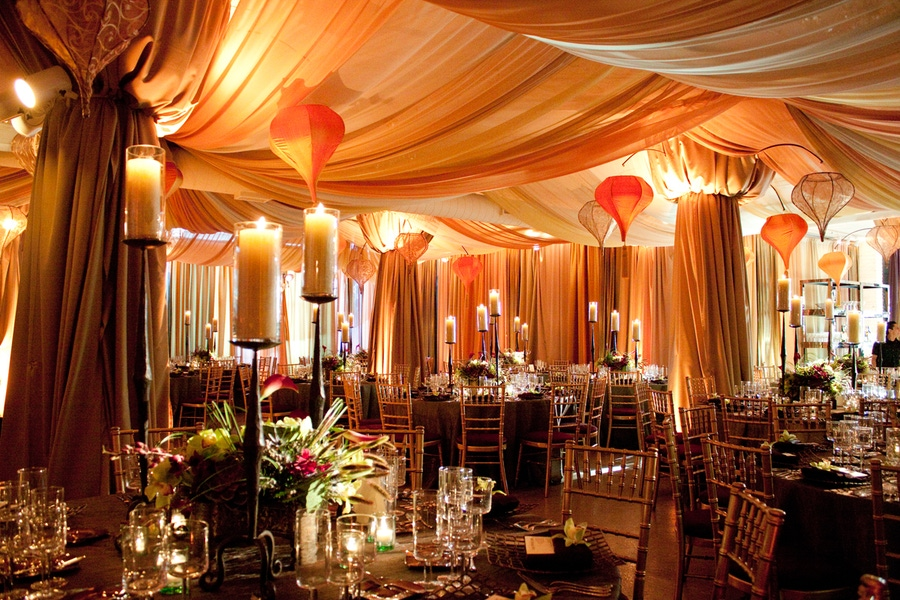 Moroccan feel with hanging lanterns, orange drapery, and gold accents