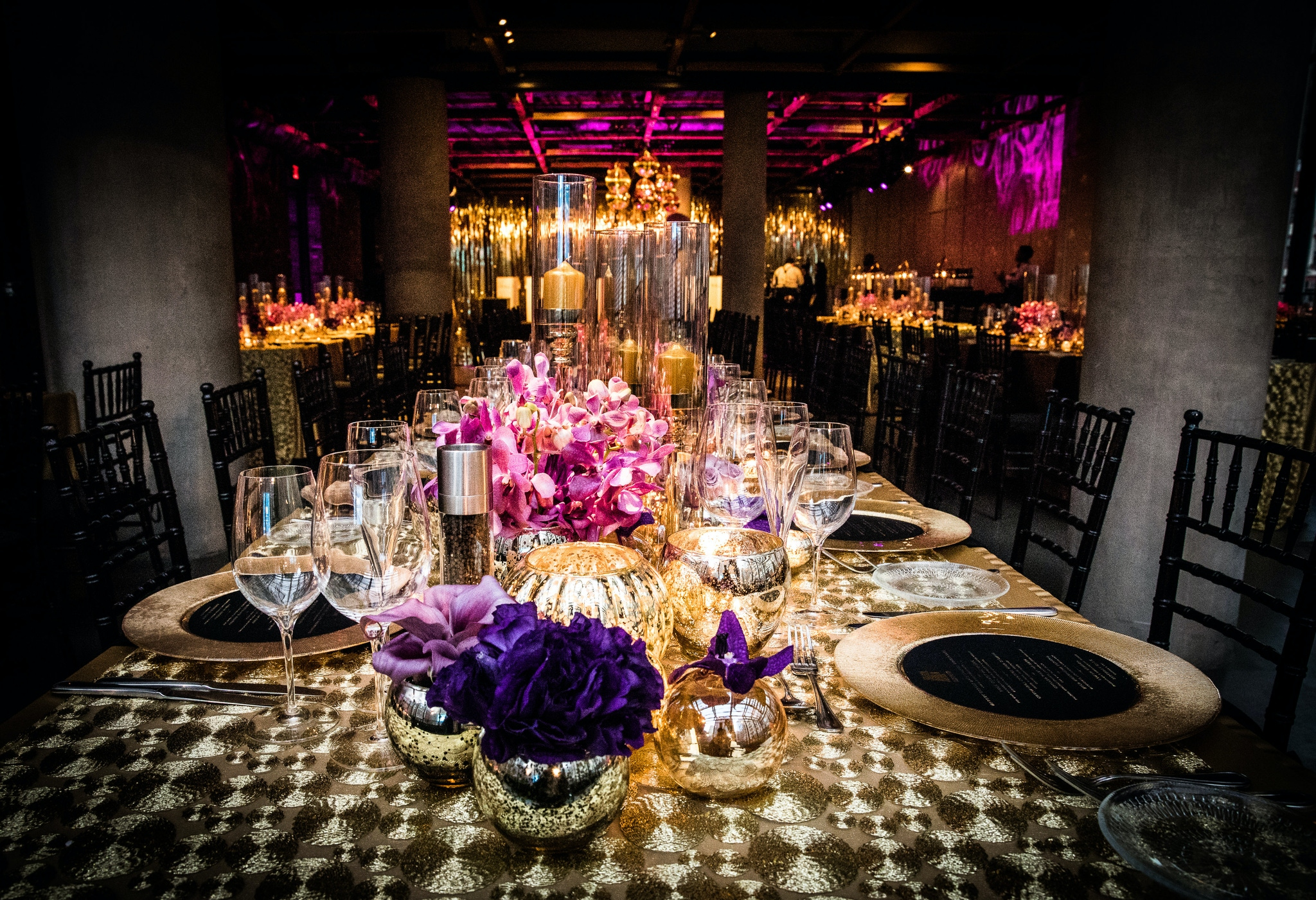 Pink and purple lights and flowers with gold records as plates at a venue in New York
