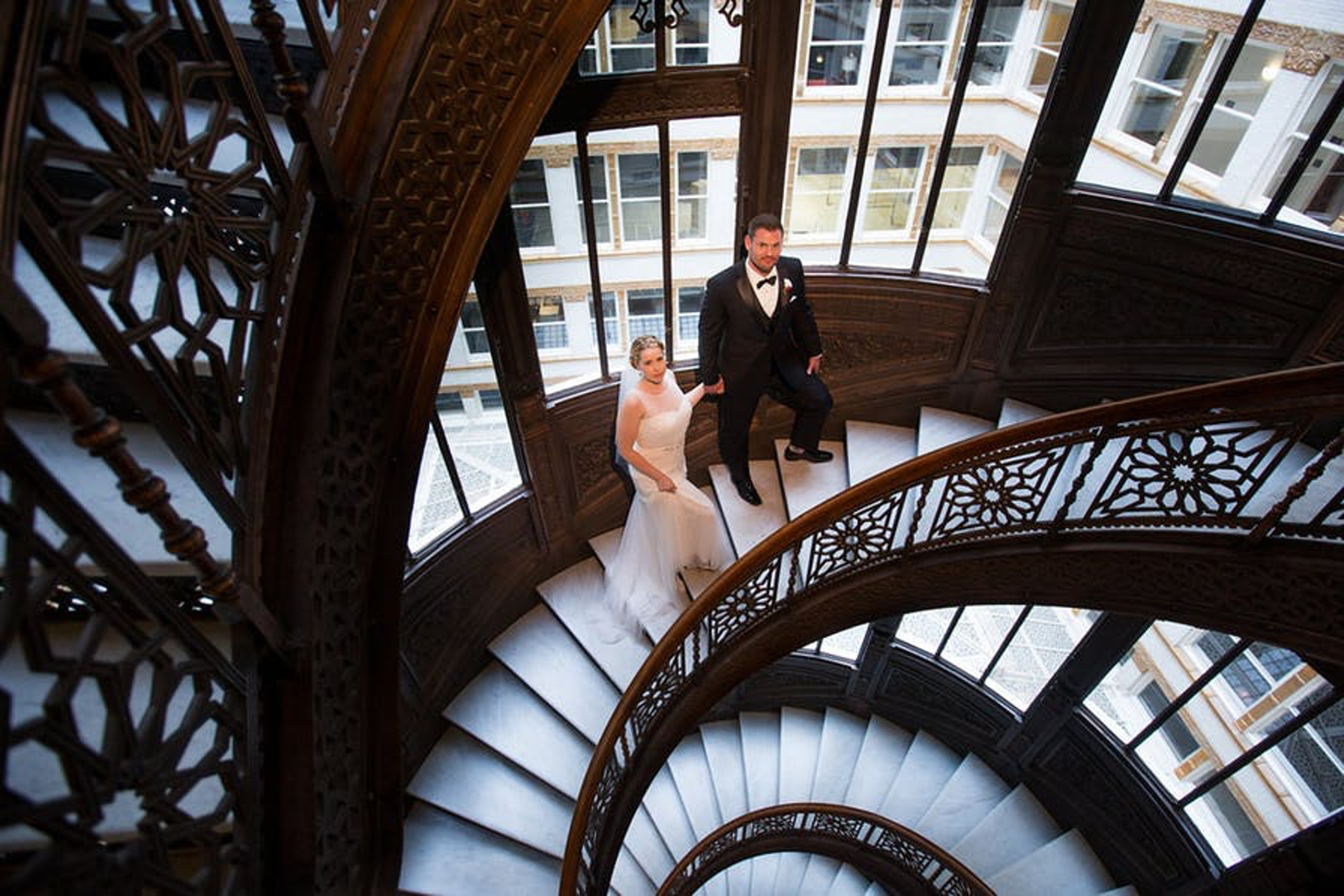 Bride and groom on winding staircase at The Rookery in Chicago