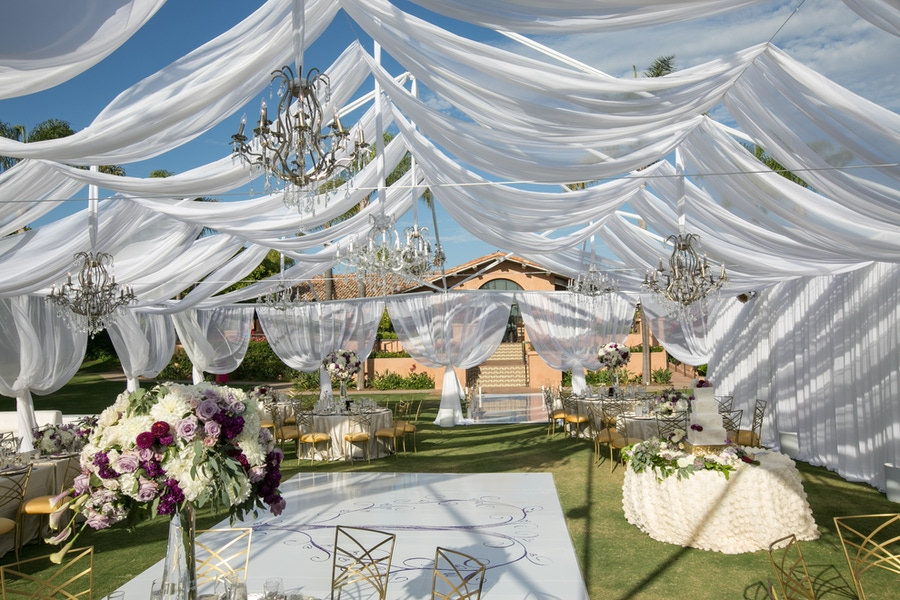 White tent with hanging chandeliers