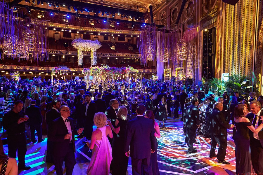 Guests in a large blue and pink lit ballroom