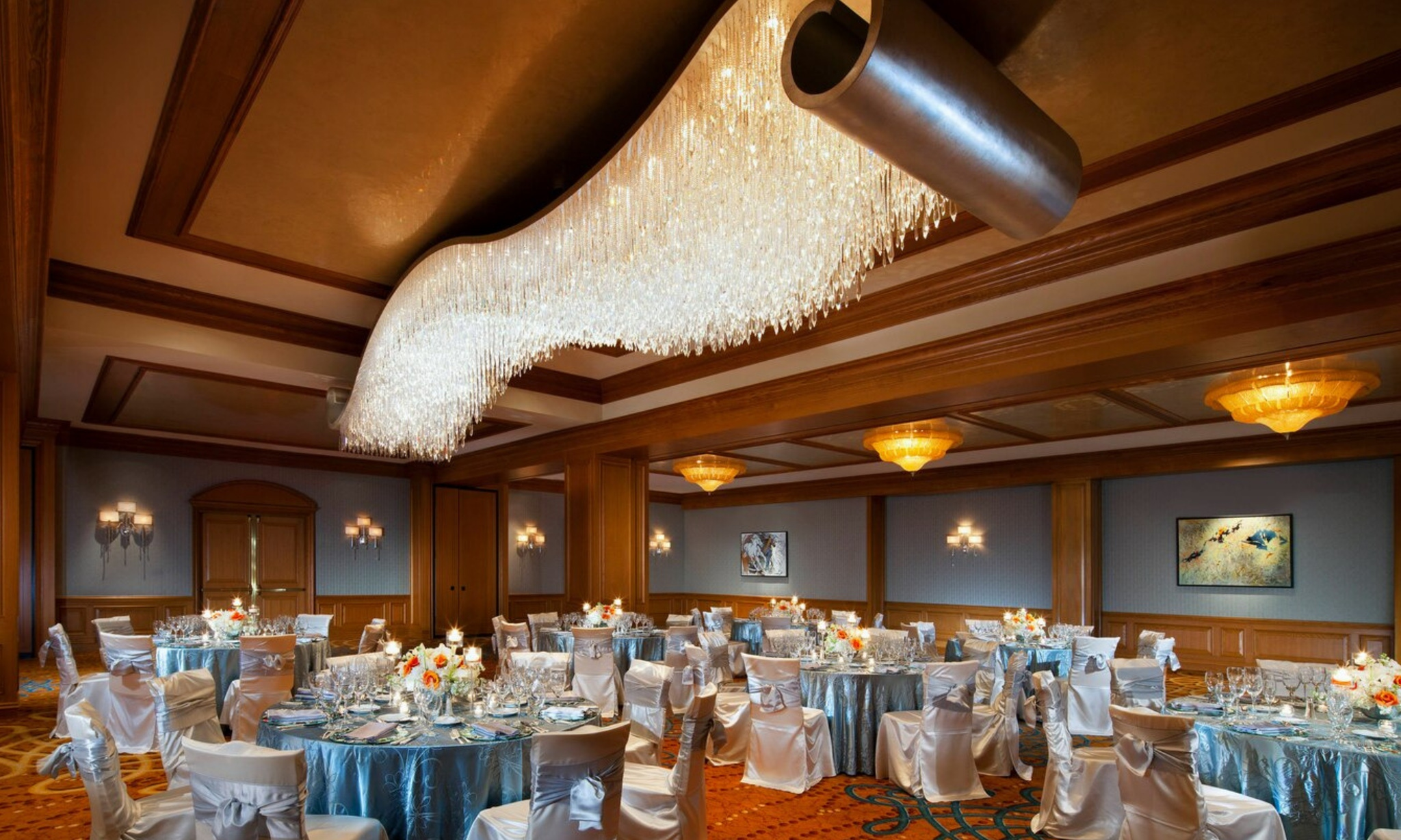 Crystal chandeliers and silver table setting at St. Regis Houston