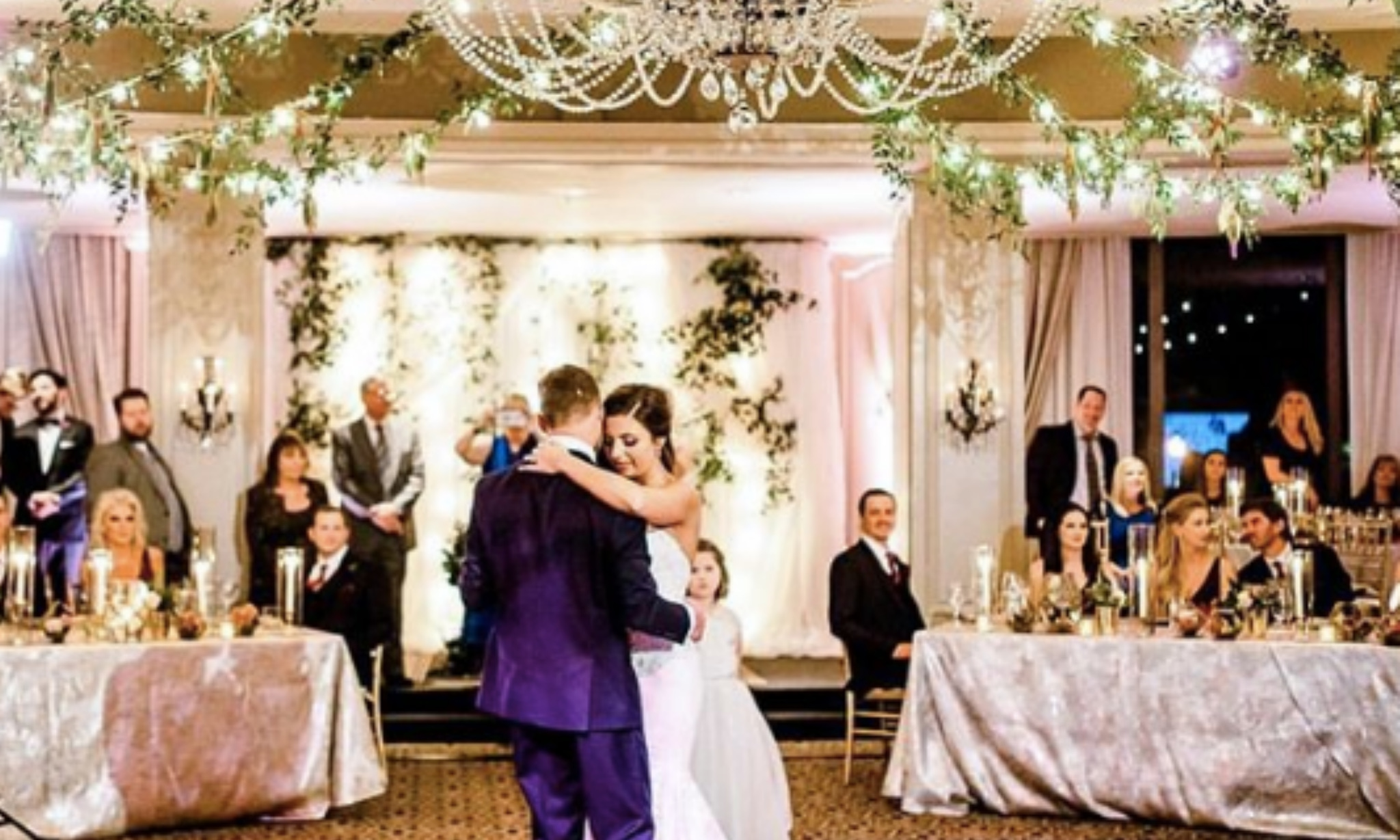 Bride and groom dance under crystal chandeliers with green decor