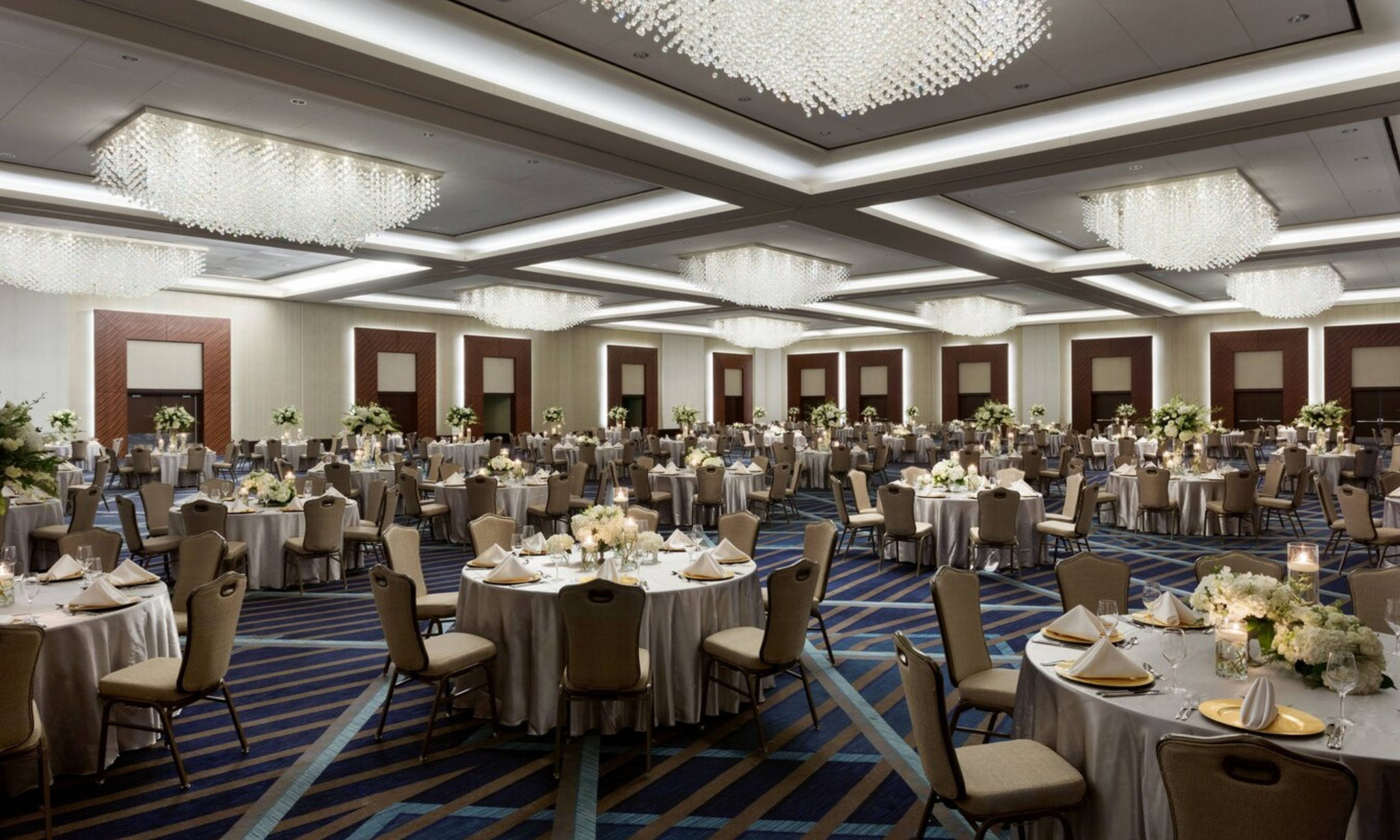 Blue carpet, gold chairs and crystal light fixtures at Marriott Marquis Houston ballroom