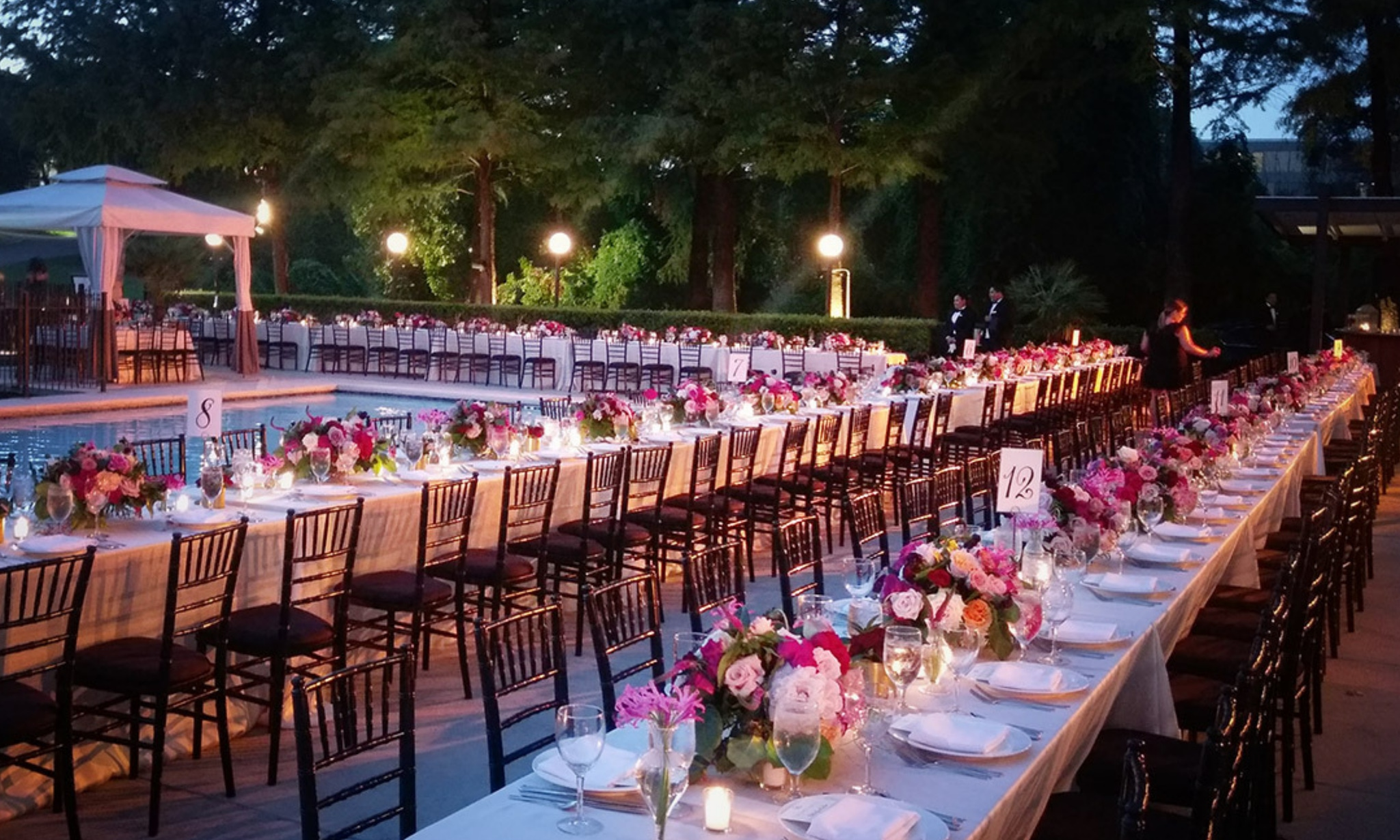 Outdoor party with pink and white florals and tables surrounding a pool