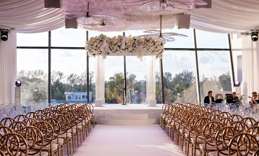 White floral chuppah and gold chairs at wedding