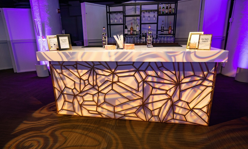 Gold designed bar with purple lighting at River Roast Social House