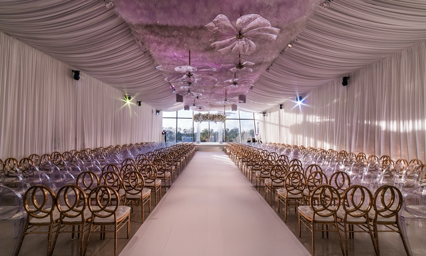 white wedding draping and decor and gold chairs at reception