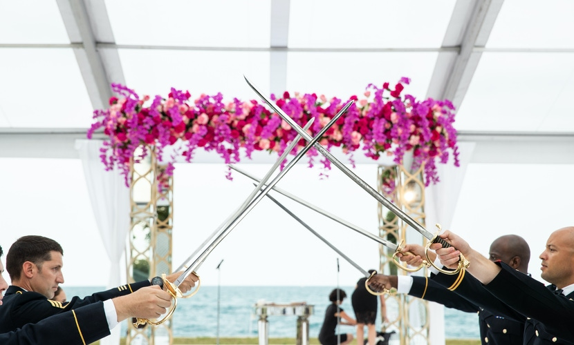 Pink floral chuppah and men with swords wedding