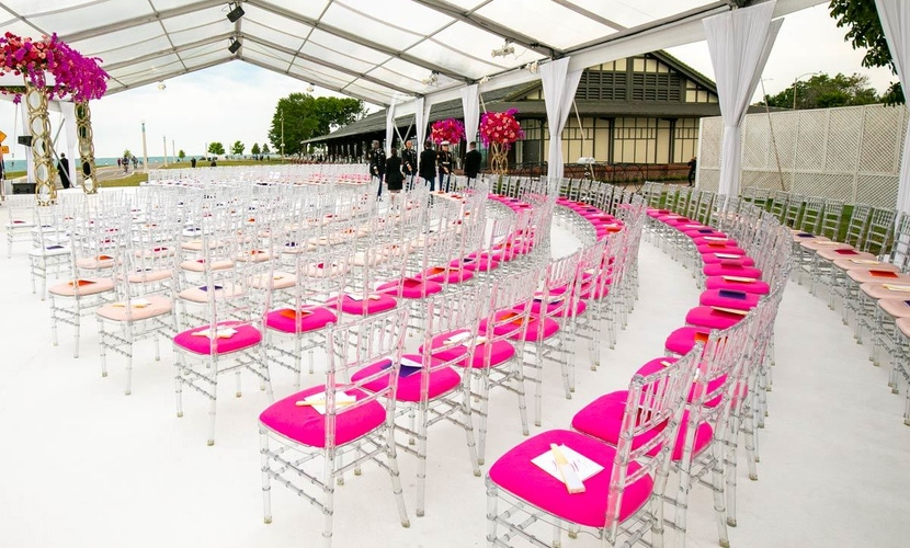 Chic ghost chiavari chairs with pink seat covers at wedding reception