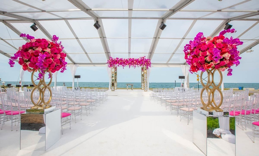 pink florals draped chuppah with pink and white accents at wedding reception