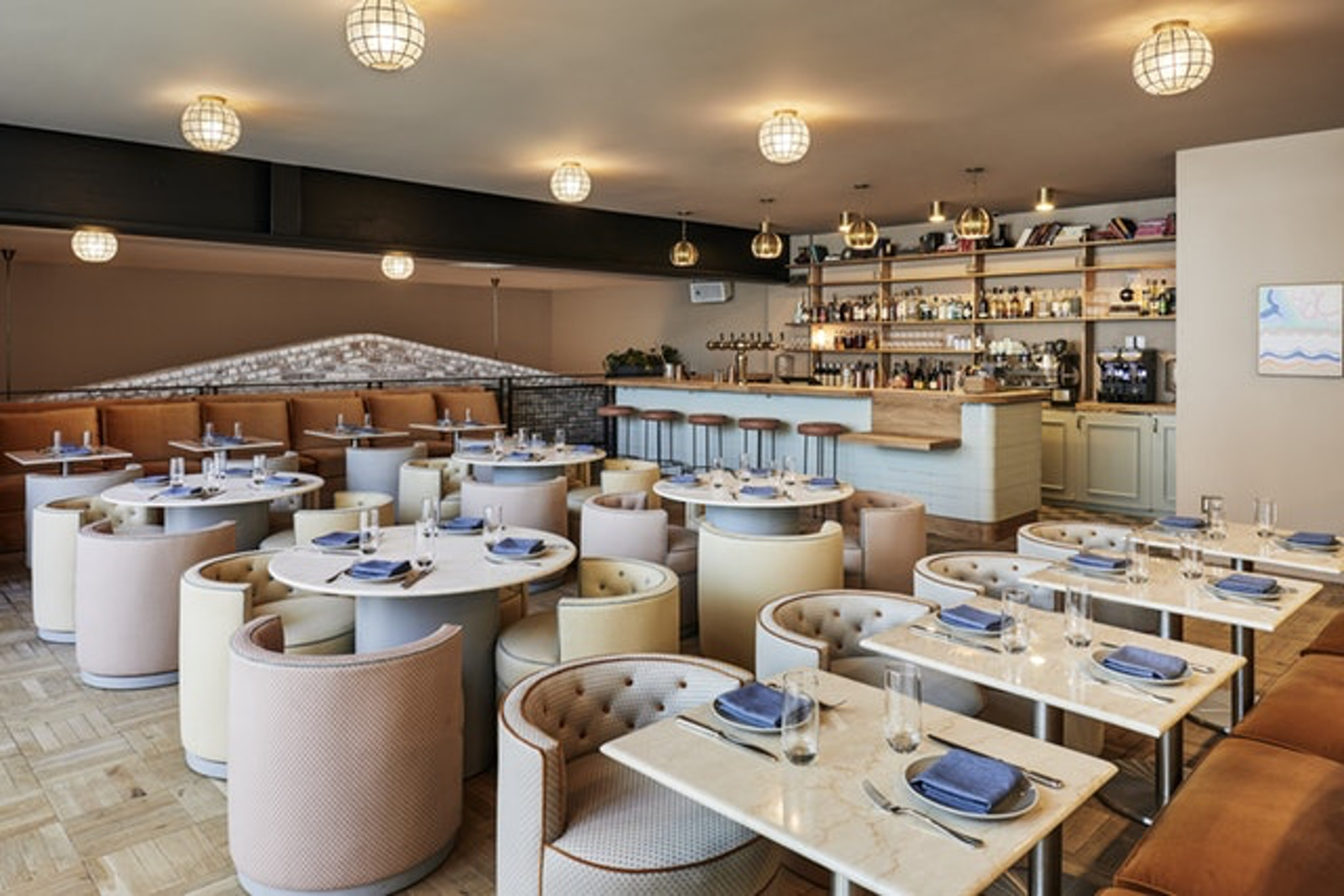 Luxe modern boutique hotel with four beige chairs and blue table setting