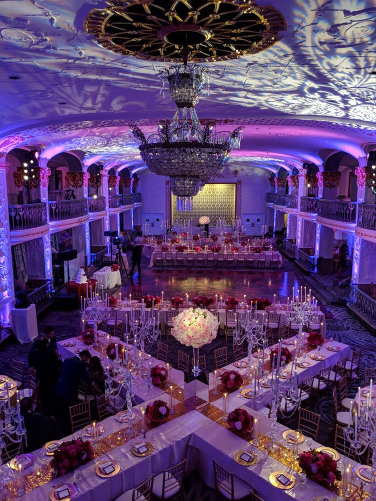 Criss cross white tables with crystal accents and purple lighting