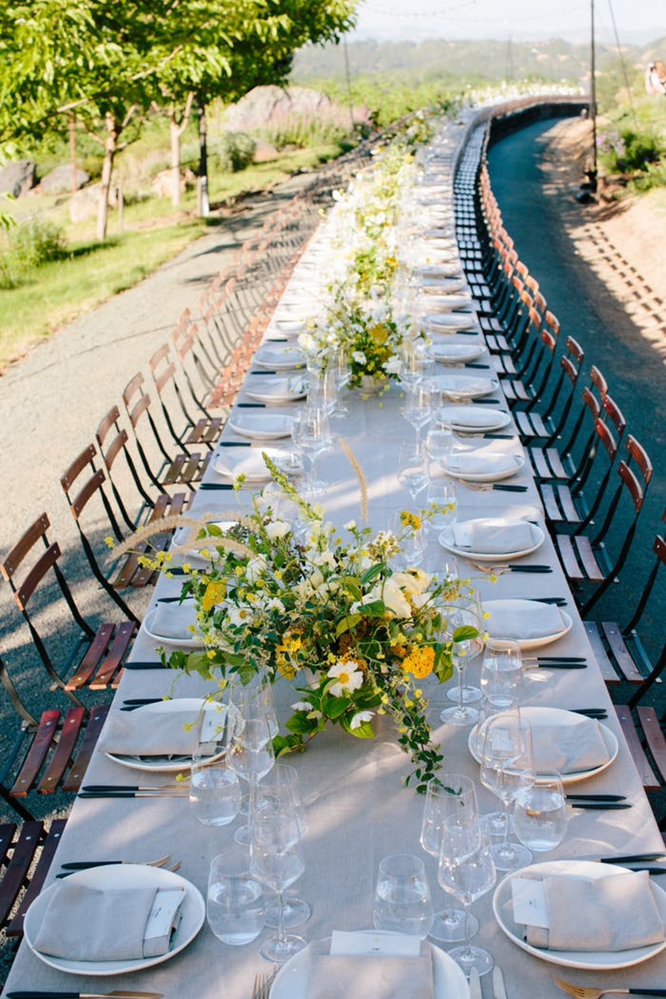 Long wedding table outside with wood chairs