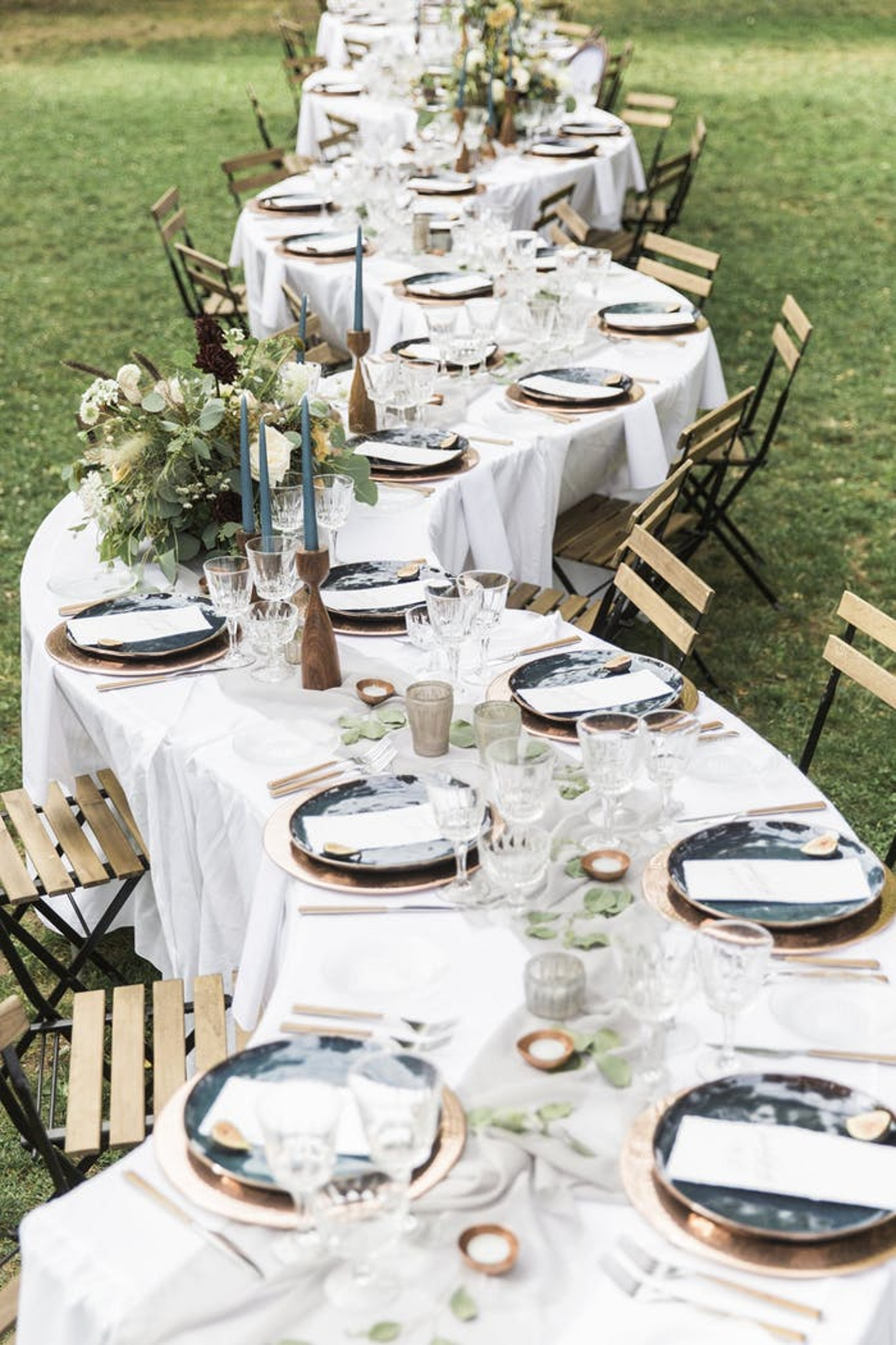 White winding wedding table with green accents and wooden chairs