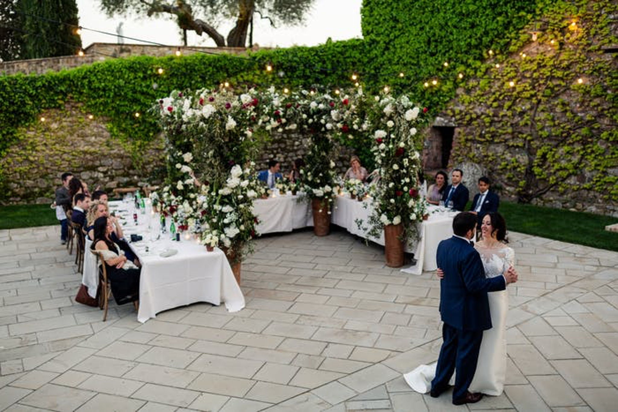 Outside wedding with lots of greenery and long white tables