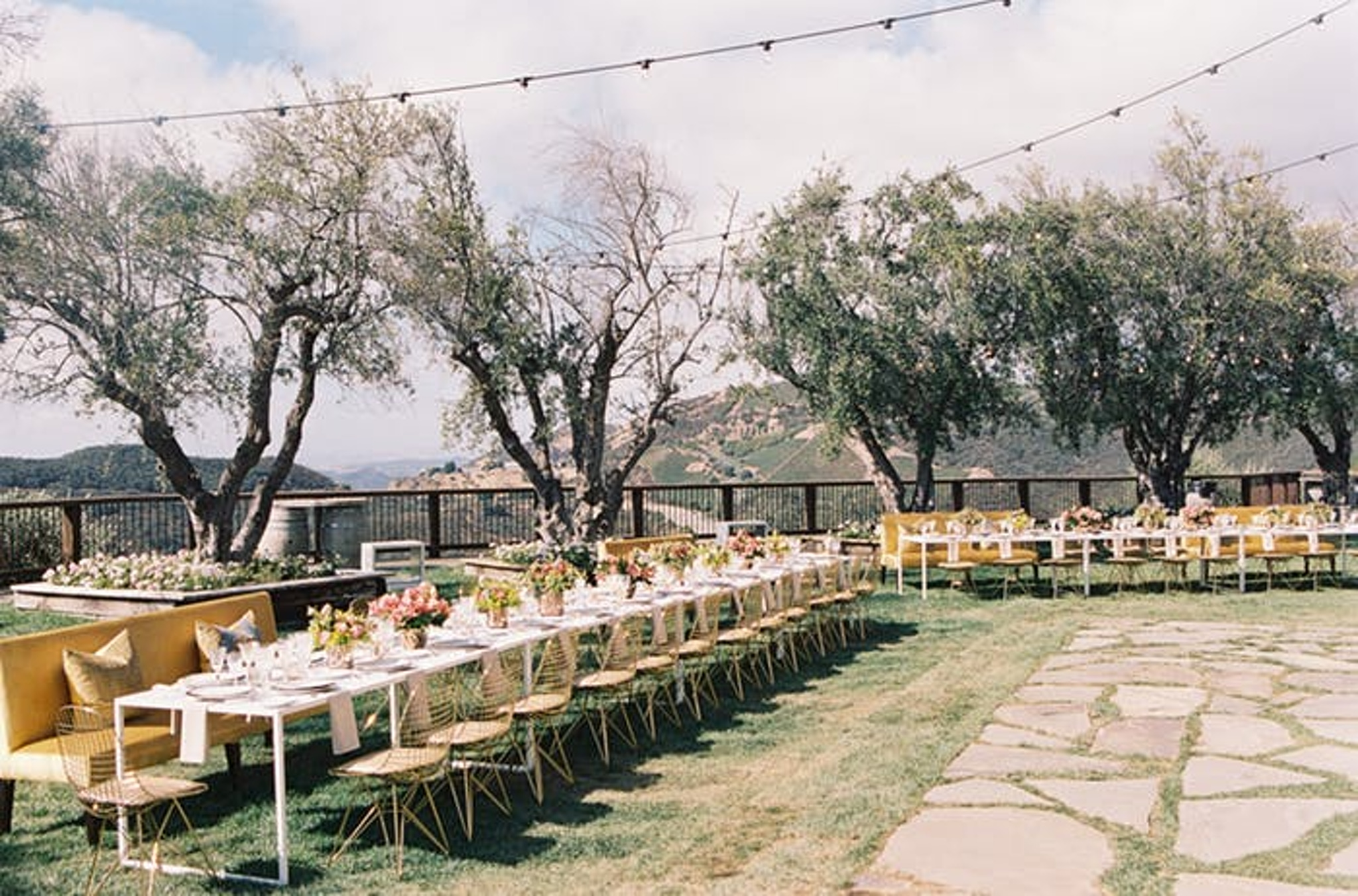 Outside long wedding tables with yellow chairs