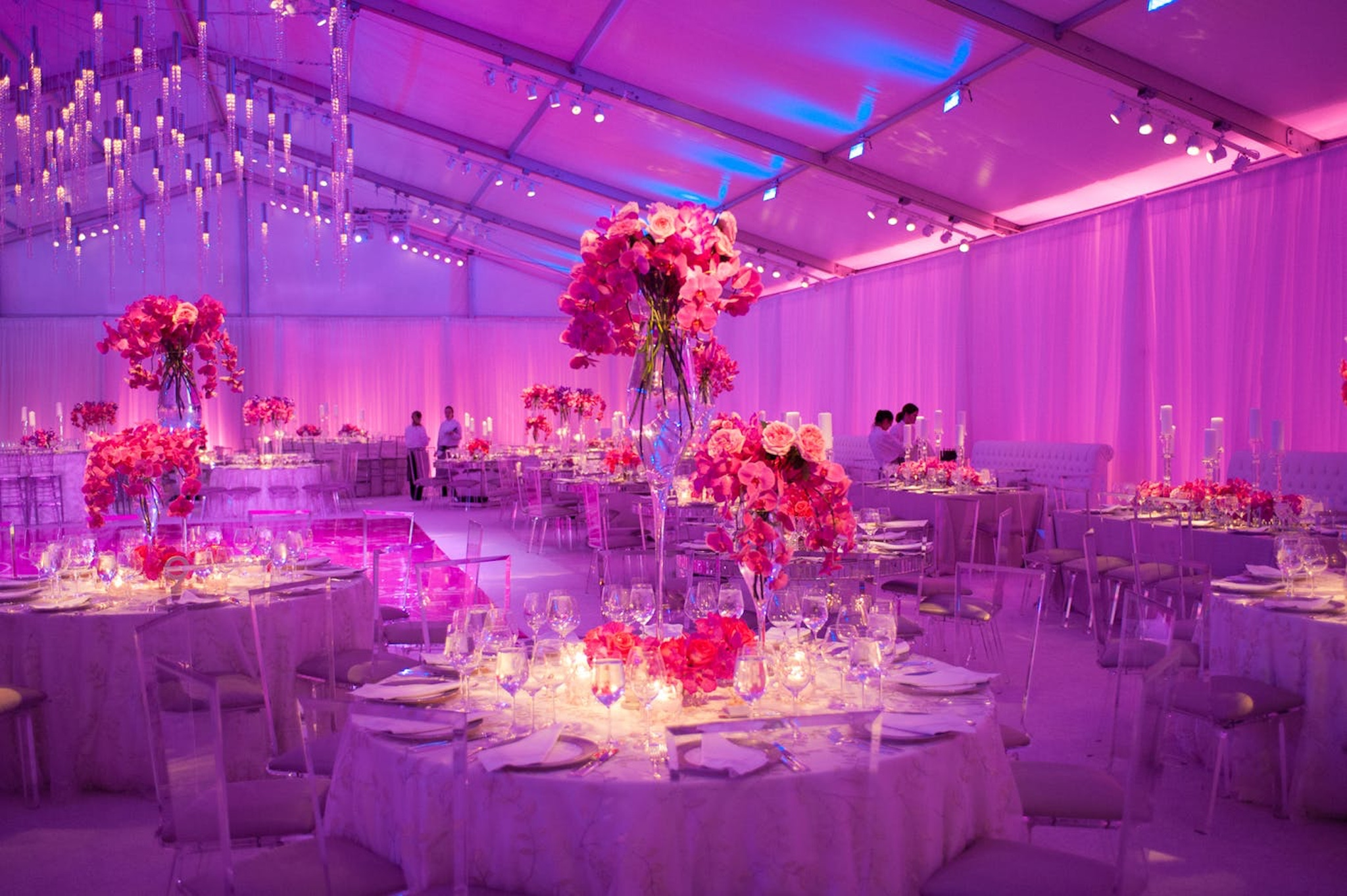 Party with big pink floral centerpieces with pink and purple lighting