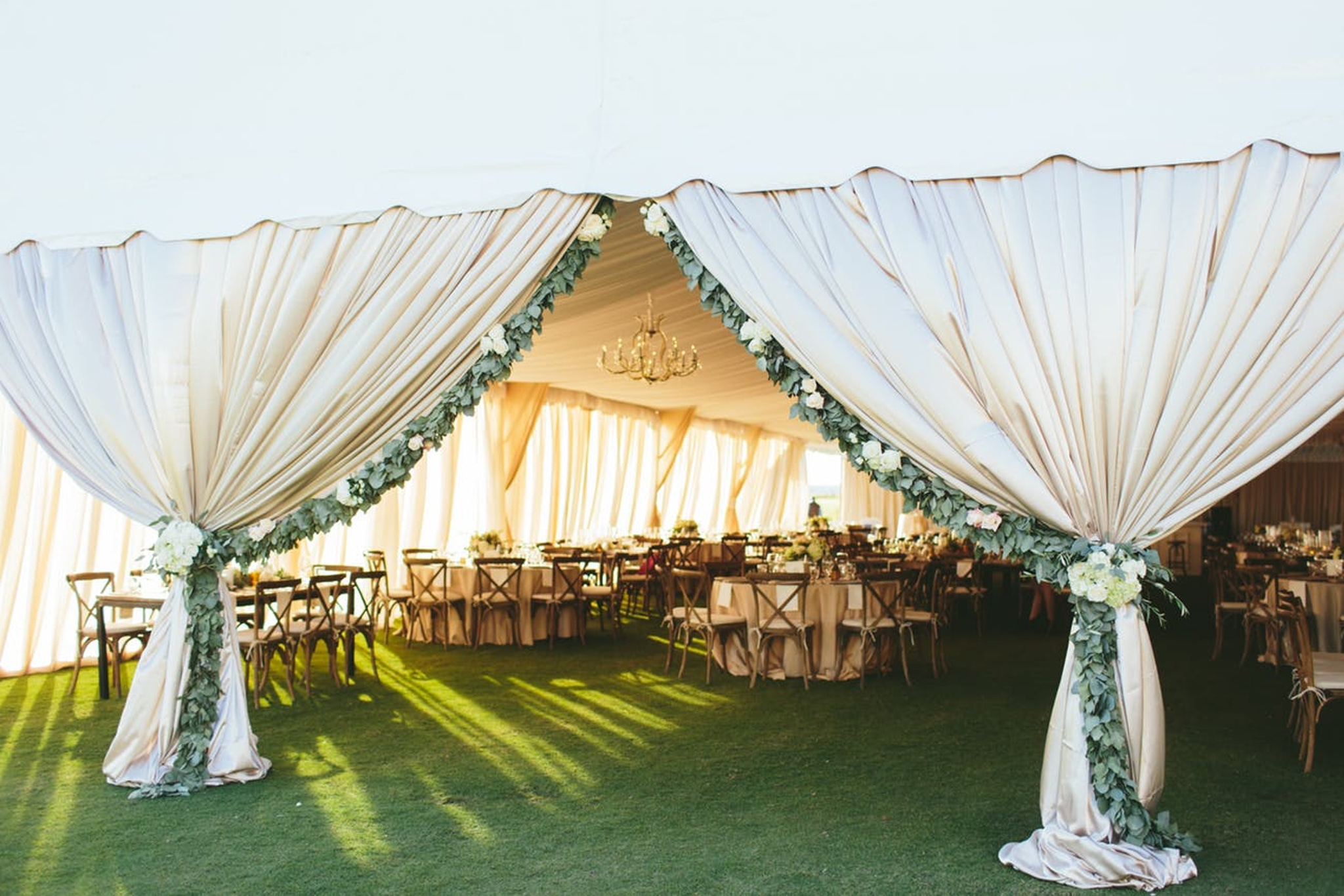 white tented wedding reception with greenery and rustic décor