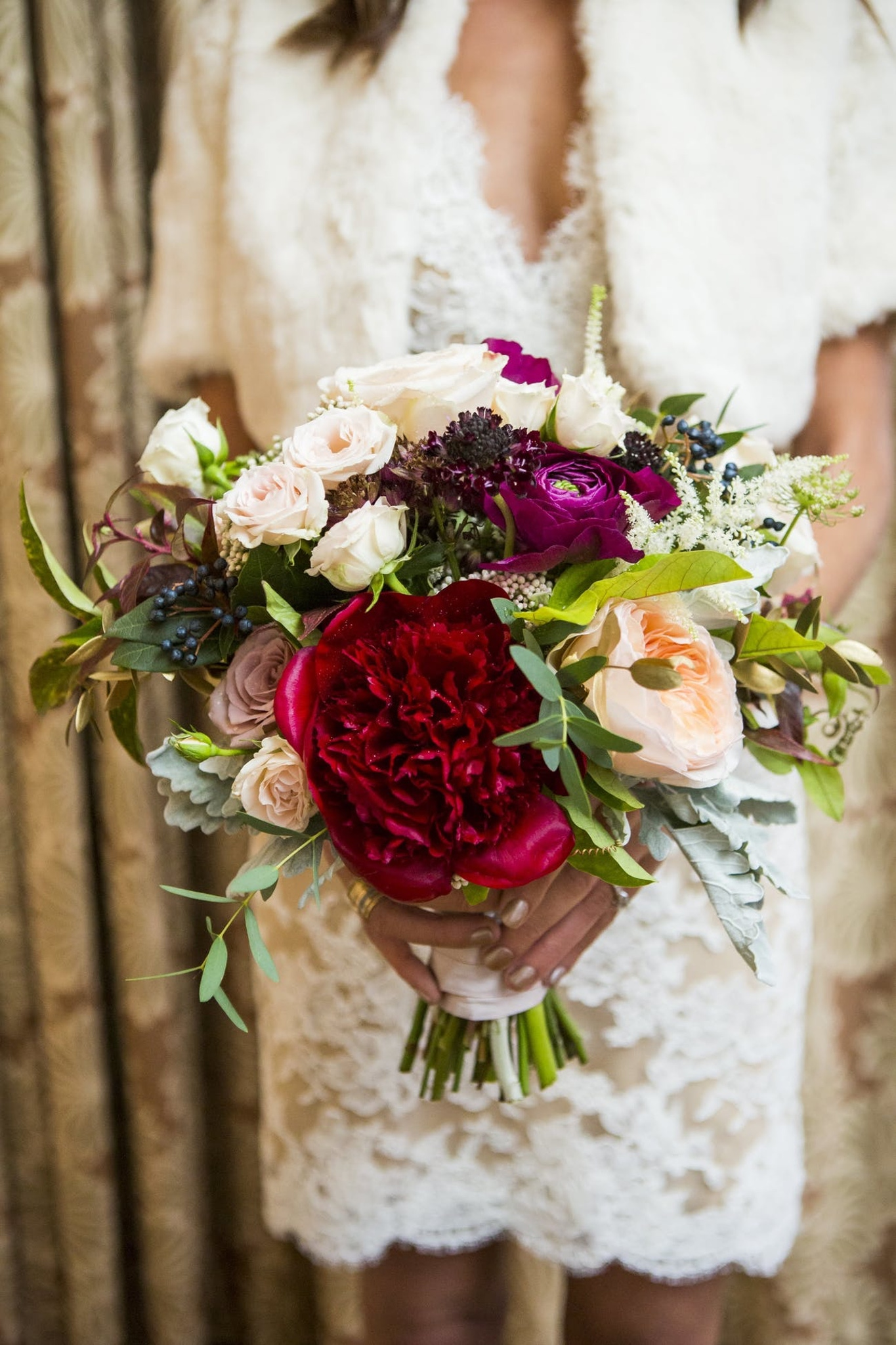 bride holding a red and white wedding bouquet with greenery for fall