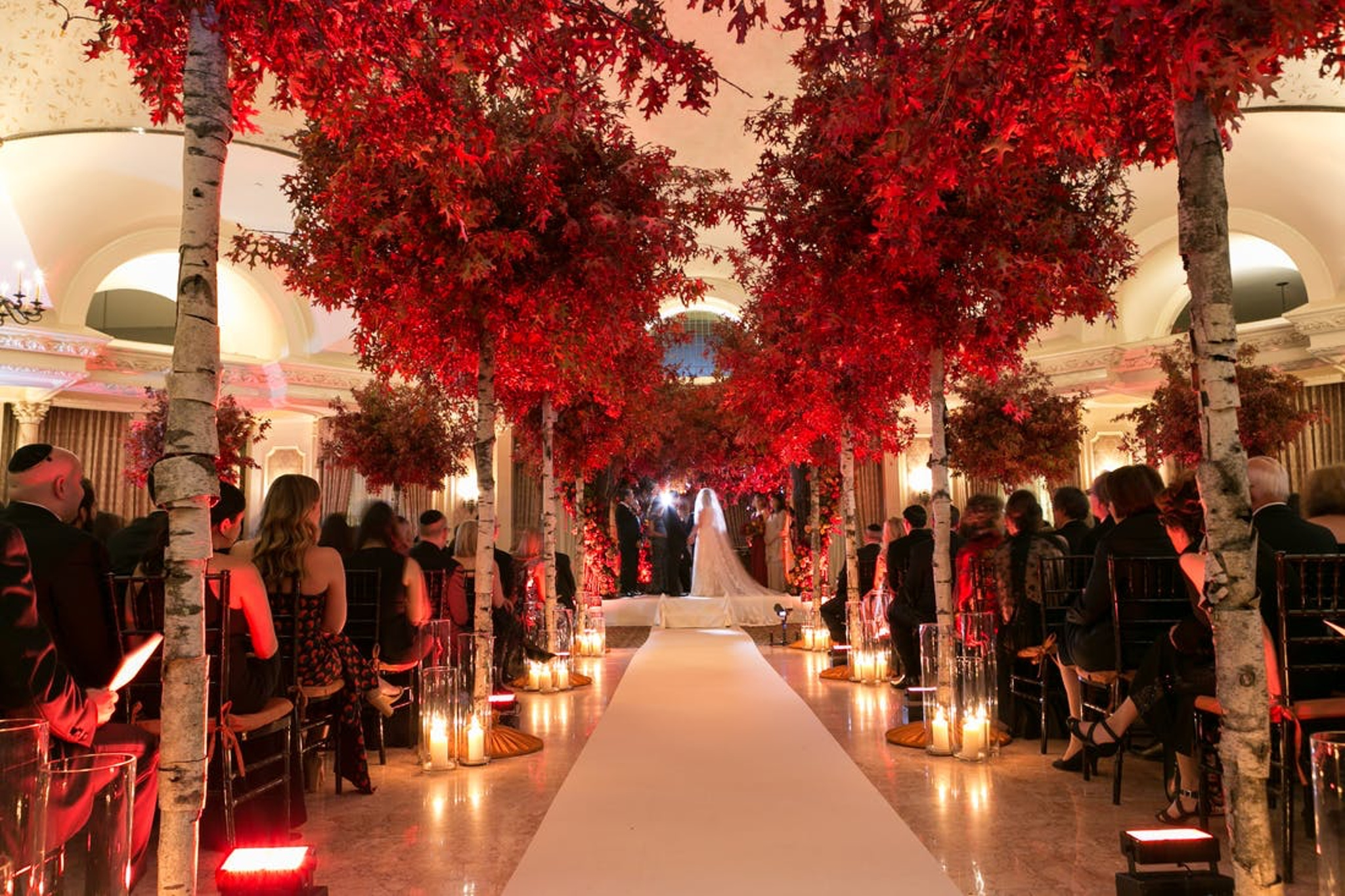 fall wedding aisle lined with romantic candles and autumn orange trees