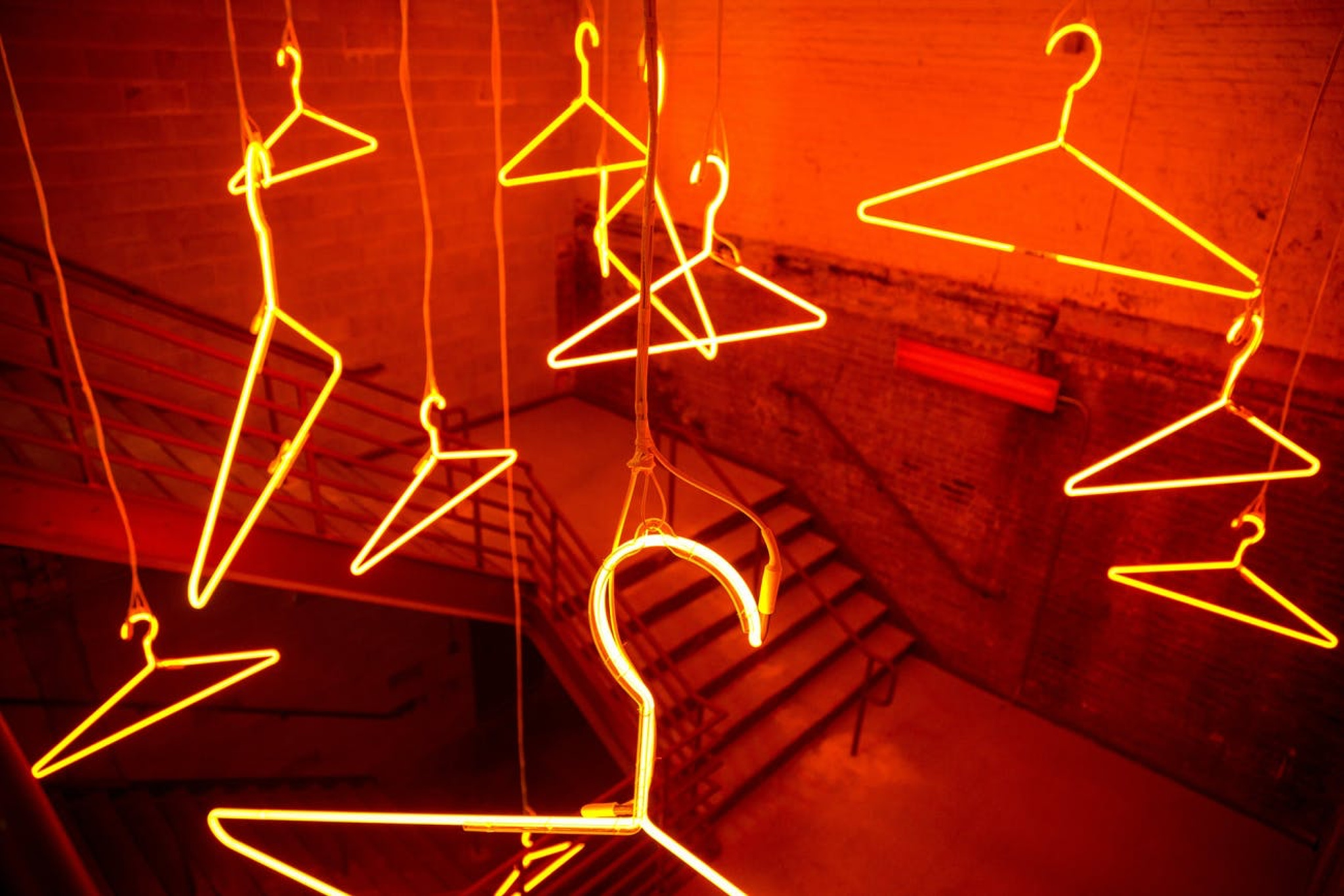 Hermés Chicago event with glowing orange hangers hanging from the ceiling