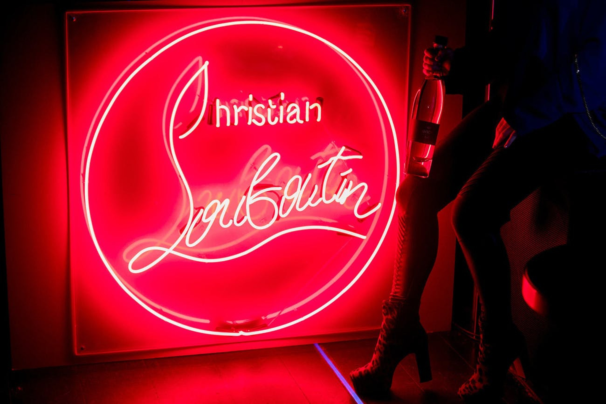 red Christian Louboutin neon signage at a Christian Louboutin fashion week after party with a red theme to match the red sole shoes