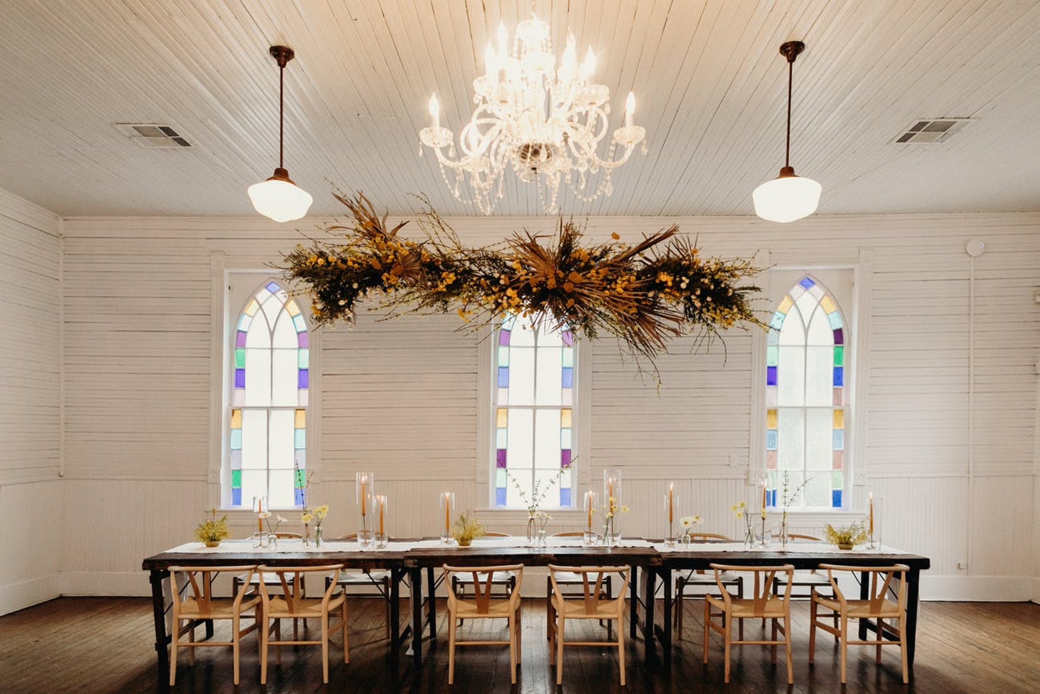 fall wedding reception table with suspended pampas grass centerpiece hovering over a rustic wood table