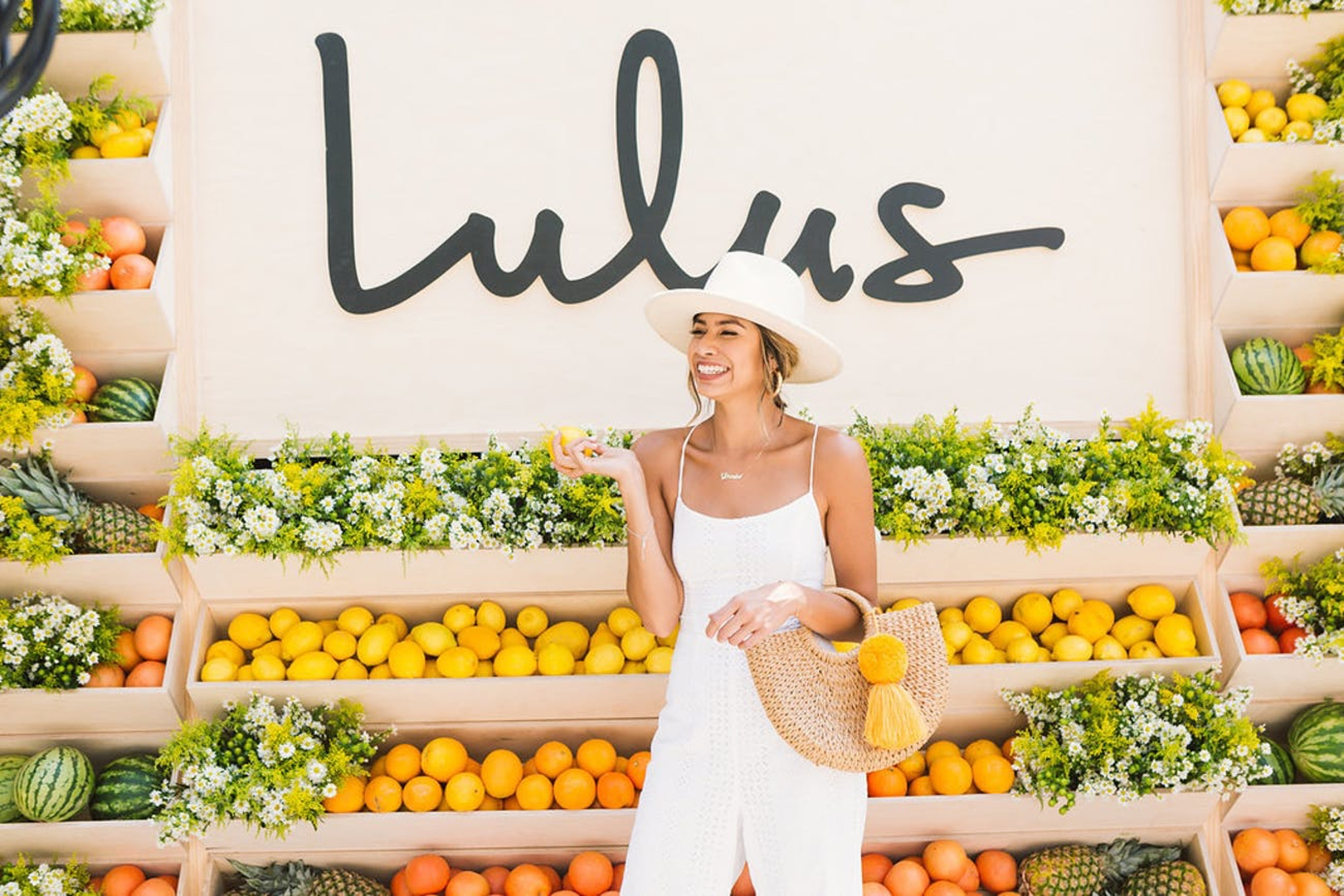 Lulus clothing store summer party with influencer posing in front of branded fruit wall
