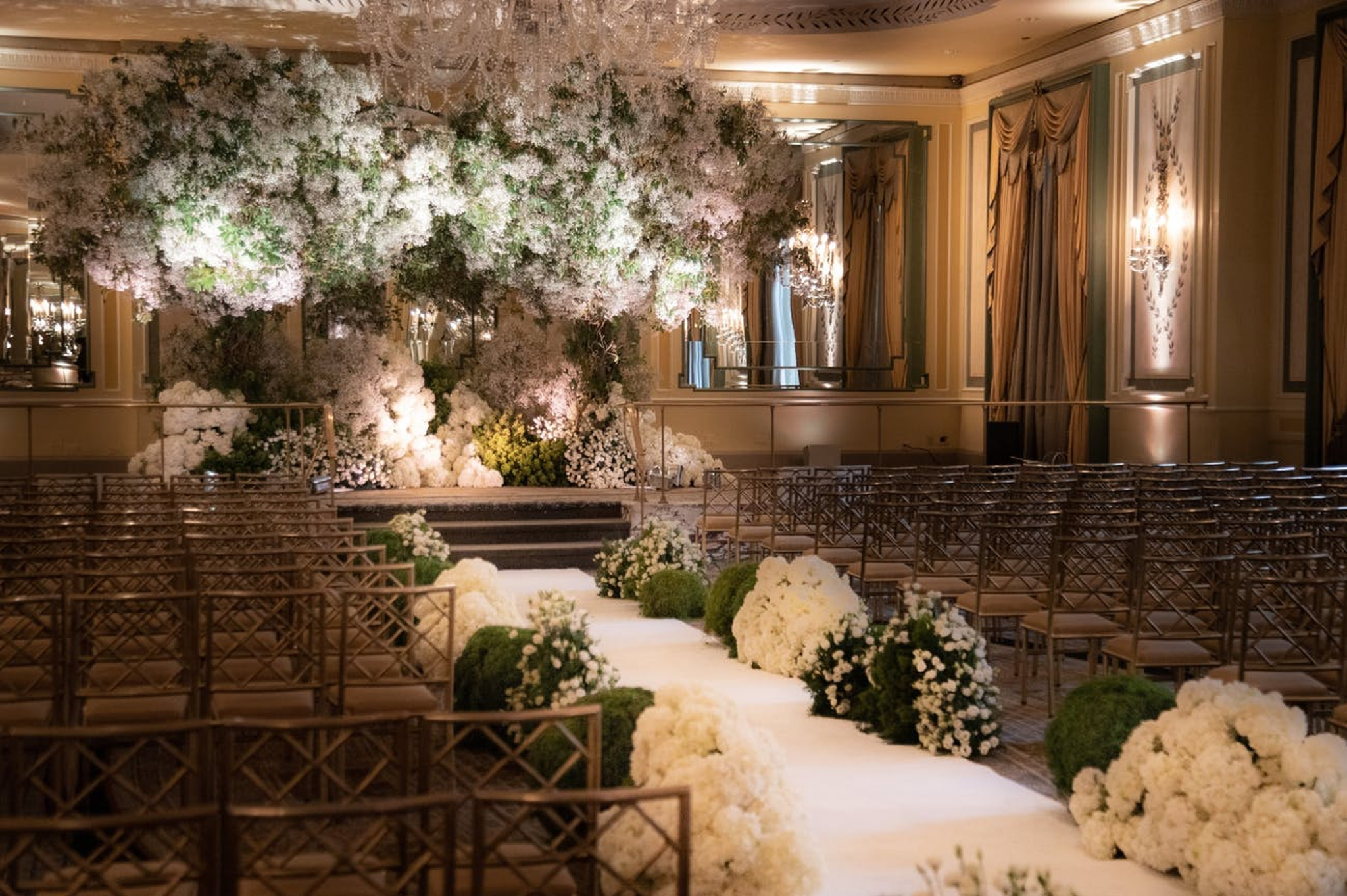 indoor wedding ceremony with white flowers and greenery and an aisle filled with white flower petals