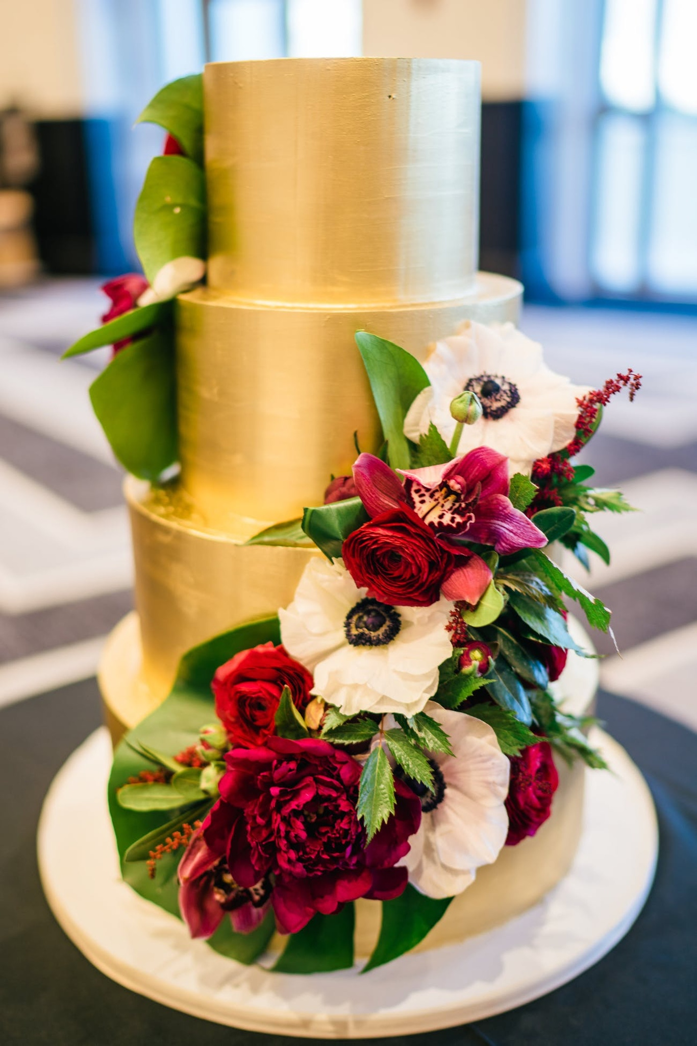 four tiered gold wedding cake with red roses and white frosted flowers