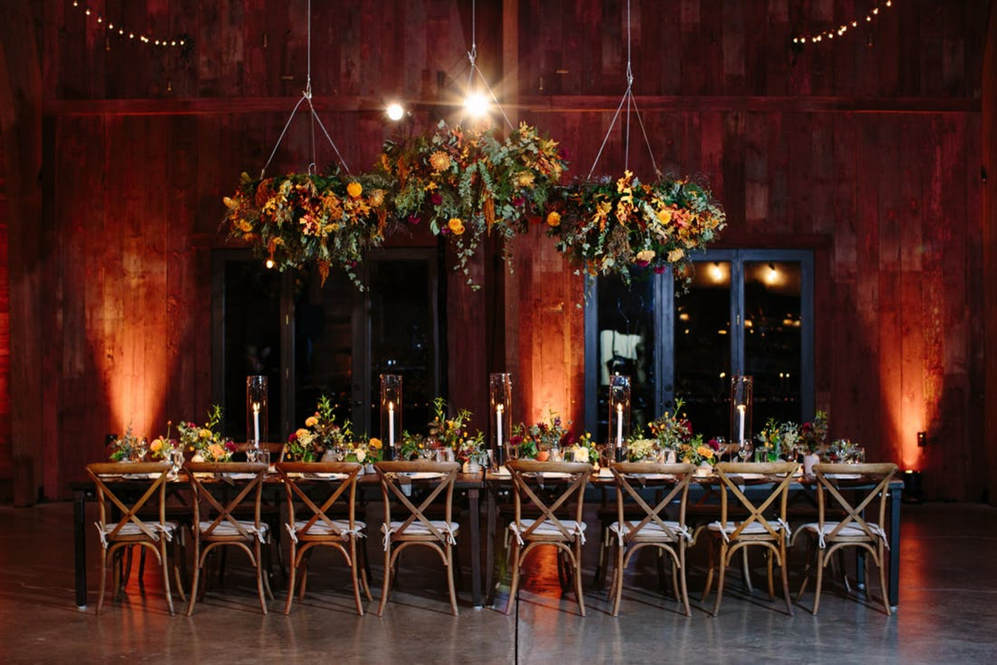 rustic boho wedding reception tablescape with elevated flower centerpieces and wood furniture