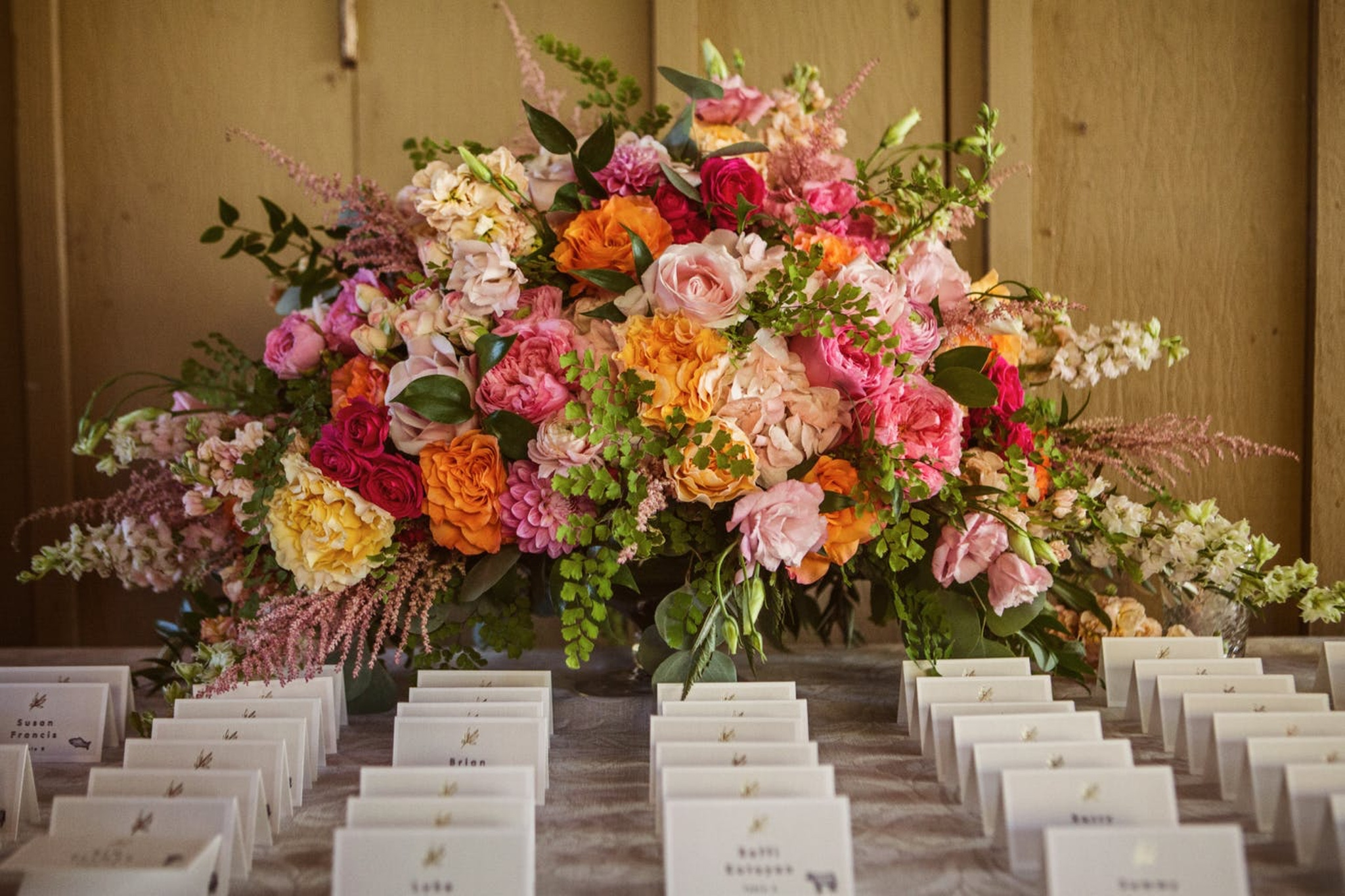 wedding seating chart with red, pink, orange and yellow floral bouquet inspired by autumn