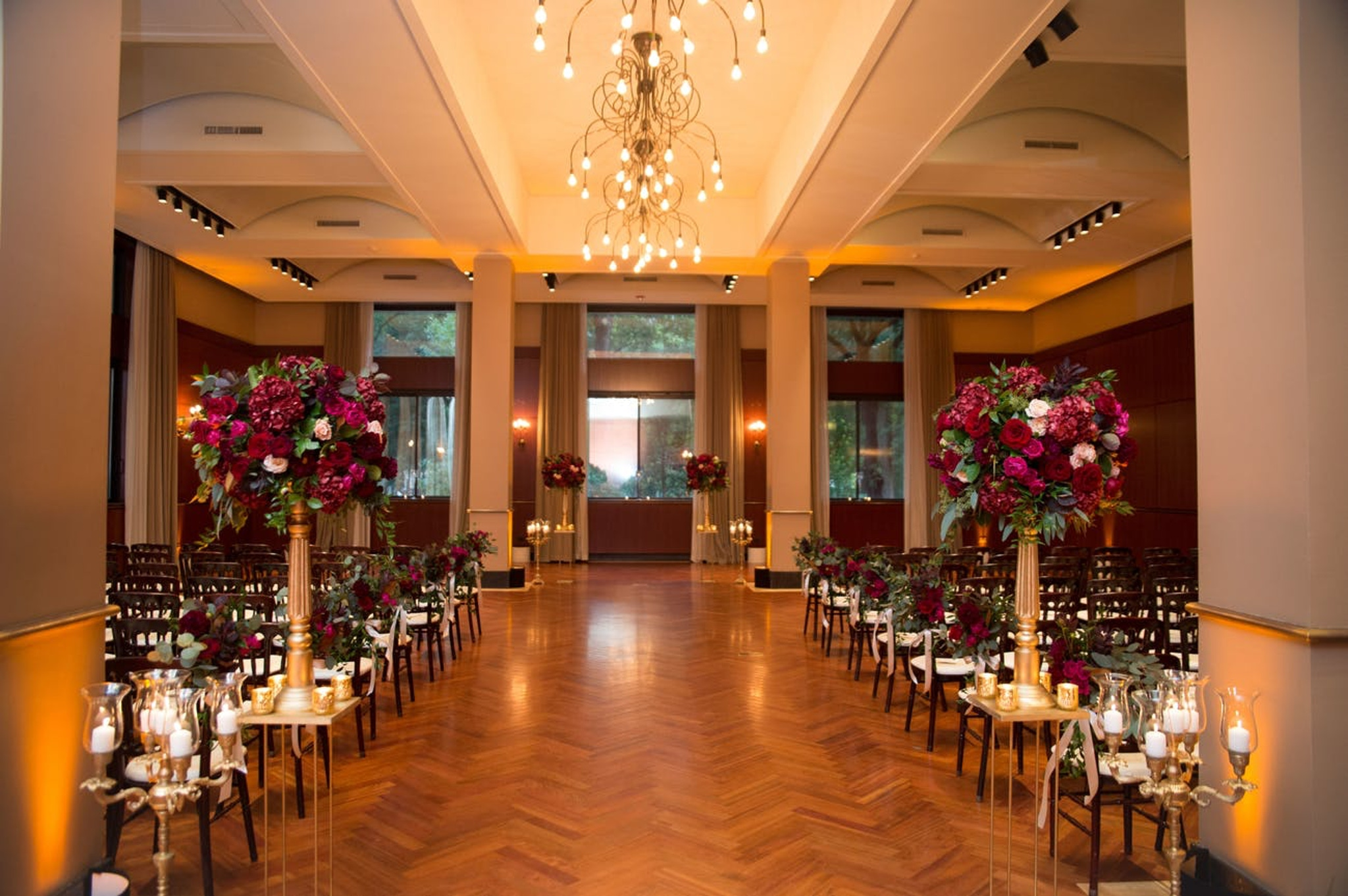 warm toned wedding ceremony aisle with wood floor and red flowers