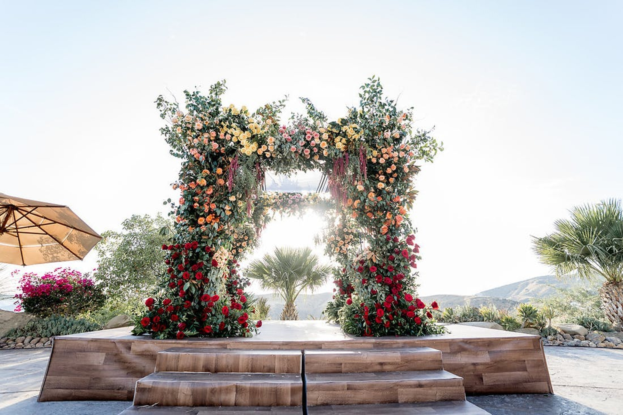 wedding ceremony outdoor floral arch with red, orange and yellow florals combined with greenery for a fall-inspired look