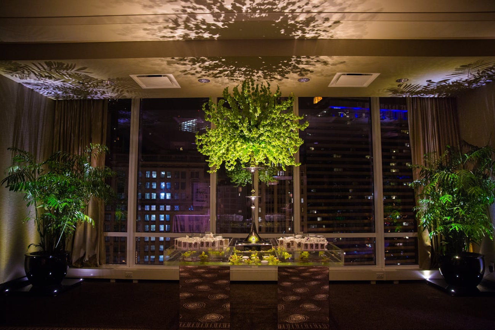 wedding reception with a city backdrop and lots of greenery